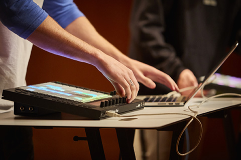 Artist uses a drum machine with a laptop on stage