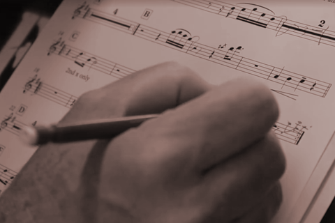 Close up picture of a hand and pencil making notes on sheet music